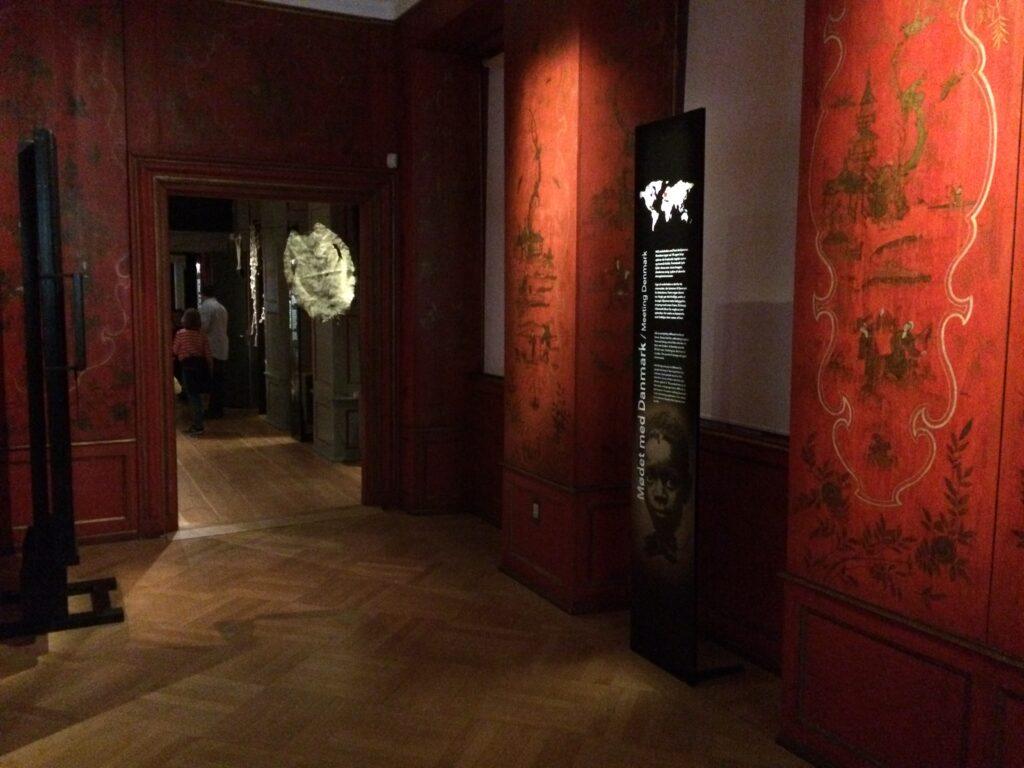 """De oprindelige røde """"kineseripaneler"""" fra udstillingsdelen """"Mødet med Danmark"""" i Nationalmuseets Stemmer fra Kolonierne. Træpanelerne, der er del af museets rokoko-interiører fra 1743-1746, indeholder et motiv af en grønlandsk kajaksejler, der formentlig er malet med inspiration fra Pôq eller Qiperoq, der i 1723 rejste fra Grønland til Danmark og sejlede i kajak gennem Københavns havn. Billede taget af Nielsen 2019."""